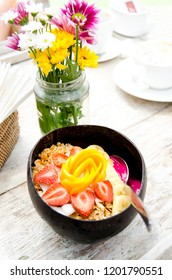 Smoothie bowl in a coconut shell bowl with strawberry; mango; dragon fruit puree and granola.