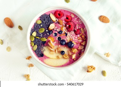 Smoothie bowl with fresh berries, nuts, seeds and homemade granola for healthy breakfast