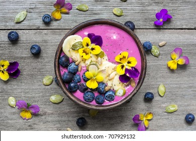 Smoothie bowl with fresh berries, nuts, seeds and flowers for healthy vegan vegetarian diet breakfast. top view