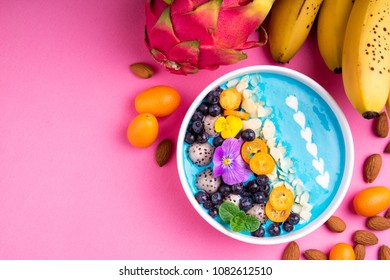 Smoothie bowl with fruits, berries, nuts and flowers. Tropical healthy smoothie dessert. Healthy breakfast, vegetarian, dieting concept. Top view, flat lay