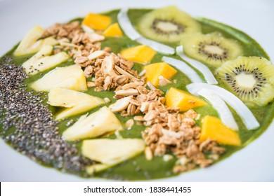 Smoothie bowl with kiwi, coconut, mango, pinapple, granola and chia seeds with green yogurt