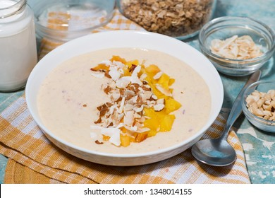 smoothie bowl with mango, coconut and nuts, closeup