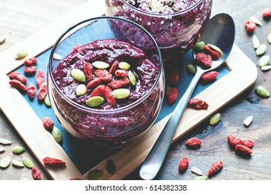 Smoothie bowl with red beets, raspberries, goji berries, hemp  and chia seeds, summer detox meal, clean eating vegetarian, vegan, superfood and healthy diet concept, selective focus, toned image