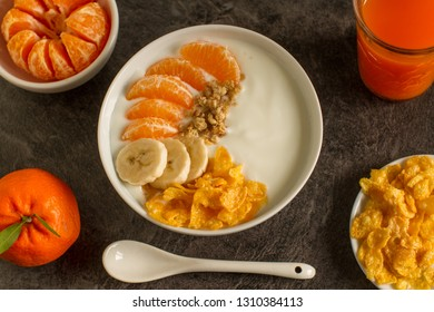 Smoothie bowl with tangerines,bananas,  granola and walnuts from above