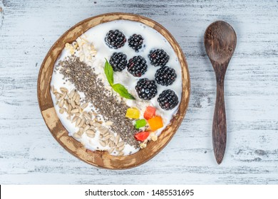 Smoothie in coconut bowl with blackberries, oatmeal, sunflower seeds and chia seeds for breakfast , close up. The concept of healthy eating, superfood. Top view