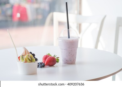 smoothie in plastic cup and frozen yogurt with fruits at the white table