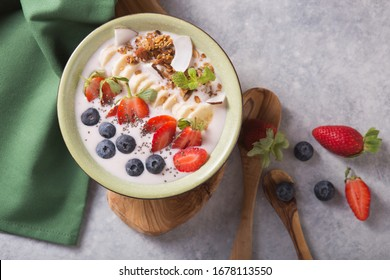 Smoothie or smoothy bowl with granola, fruits and seeds.  Organic probiotic drink or yogurt  with strawberry, on the white grey background. Trendy food. Copy space