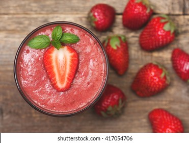 smoothie with strawberries in a glass, fresh strawberry on old wooden background (top view)
