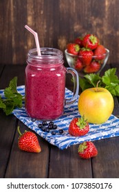 Smoothie from strawberry, blueberry, apple and banana in glass mug on wooden table, close up