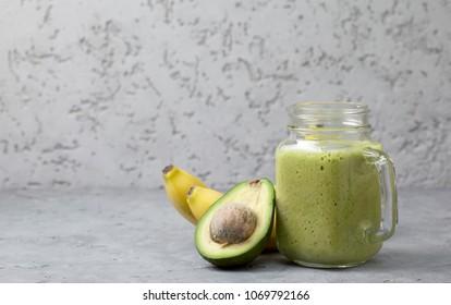 smoothies avocado banana in a mason jar, bananas and avocado on a gray concrete background
