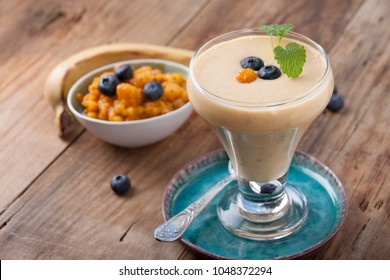 Smoothies with cloudberries, a banana and a blueberry  in a glass on a turquoise plate on an old wooden table