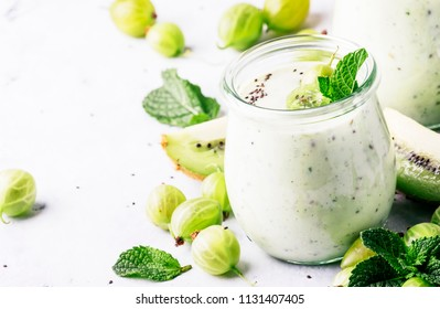 Smoothies from gooseberry, kiwi and yogurt with chia seeds, gray background, selective focus