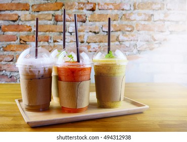 Smoothies and iced coffee in plastic cup on wooden tray and brick wall background in cafe. Take away drinks concept.