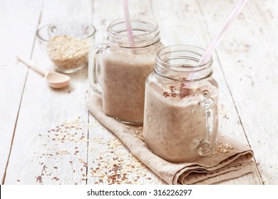 smoothies with  oatmeal,  flax seeds in glass jars on a wooden background