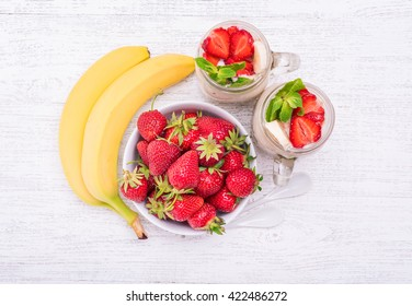 Smoothies with oatmeal ,strawberry, banana in glass jars on a wooden background.