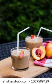 smoothies from peach, in glasses with straw, cut slices of peach, on a wooden tray, in the open air