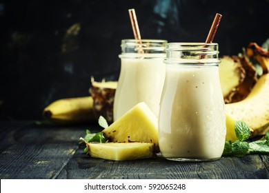 Smoothies from pineapple and banana in glass bottles, dark background, selective focus