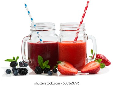 Smoothies from summer berries ( strawberry; blueberry and blackberry ) in mason jars with straws isolated on white background.