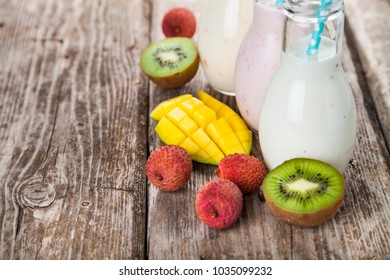 Smoothies with tropical fruits on a wooden background. Tasty breakfast. Healthy eating.
