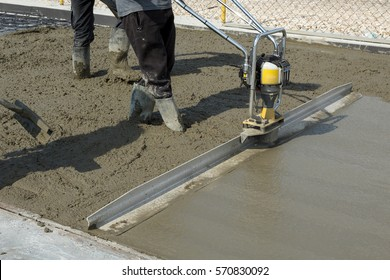 Smoothing fresh concrete with gas powered vibrating screed machine on a construction site