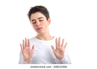 smooth-skinned Caucasian teen in a white long sleeve t-shirt uses downward hand gestures showing palms with both hands exposing wrists meaning he's telling the truth and he should be trusted
