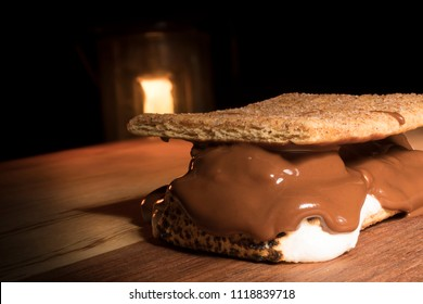 Smore with chocolate melting and a camping lantern behind