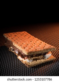 Smore fresh off the campfire with orange light coming from the right