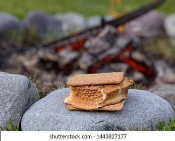 s'more sitting on edge of rock firepit with blurred burning embers in background