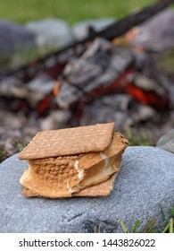 s'more sitting on a rock in front of a blurred fire in the background