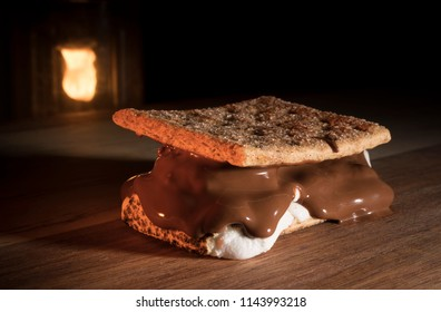 Smore with thick marshmallows and chocolate and camping lantern behind