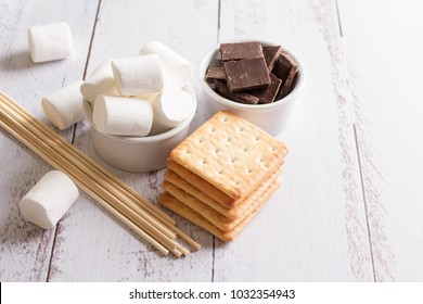 Smores dessert ingredients on wooden table. Picnic or camp concept. Homemade S'more with chocolate and marshmallow on cracker.