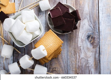 Smores dessert ingredients on wooden table. Picnic or camp concept. Space for text