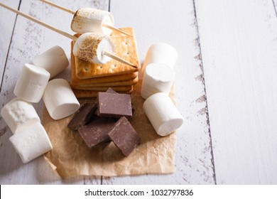 Smores dessert ingredients. Picnic or camp concept. Homemade S'more with chocolate and marshmallow on cracker.