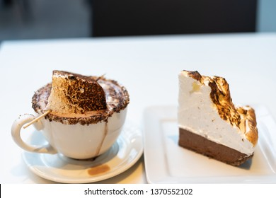 A smores hot chocolate and smores pie. The photo is mostly white, with the delicious looking food serving as a contrast point.