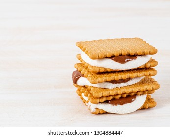 Smores, marshmallow sandwiches - traditional American sweet chocolate cookies on white wooden table, side view.