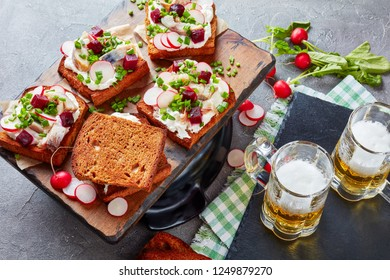 Smorrebrod - danish open faced sandwiches of rye bread, smoked mackerel slices, cream mixed with shredded horseradish, beetroot, fresh radish, onion on a cutting board with mugs of beer, close-up