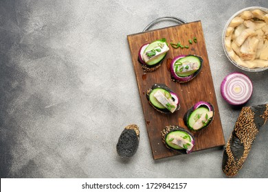 Smorrebrod, tapas or sandwich with onion, cucumber and herring  on the cutting board. Top view. Copy space