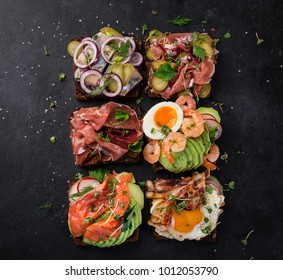 Smorrebrod, traditional Danish open sanwiches, dark rye bread with different topping, black background, top view, square image