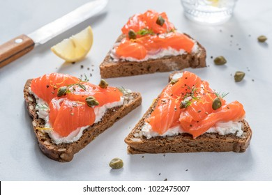 Smorrebrod, traditional Danish open sanwiches, dark rye bread with salmon, cream cheese and capers. Top view.