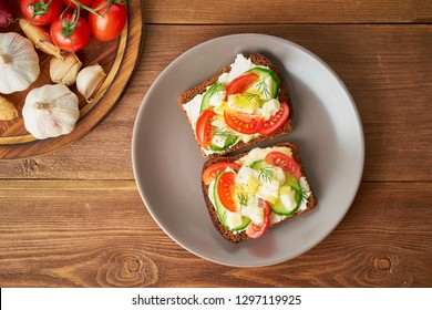 Smorrebrod - traditional Danish sandwiches. Black rye bread with boiled egg, cream cheese, cucumber, tomatoes on dark brown wooden background, top view