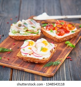 Smorrebrod - traditional Danish sandwiches. Black rye bread with fish, herring, egg, tomatoes, radish on dark brown wooden background