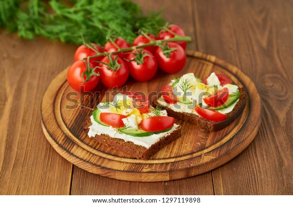 Smorrebrod - traditional Danish sandwiches. Black rye bread with boiled egg, cream cheese, cucumber, tomatoes on dark brown wooden background, side view