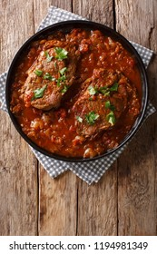 Smothered steak or Swiss steak in a spicy tomato sauce with vegetables close-up on the table. Vertical top view from above