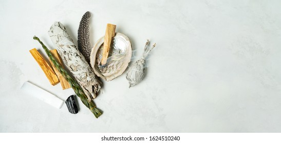 Smudge kit for spiritual practices with natural elements: Palo Santo sticks, dried white sage, Guinea Fowl feather, crystals, sea pearl shell Abalone on a light background. Balancing the soul.