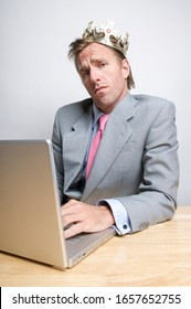 Smug businessman wearing royal gold crown sitting in front of his laptop computer