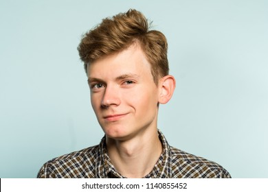 smug handsome guy with a mysterious smile. cute geek or dork. portrait of a young guy on light background. emotion facial expression. feelings and people reaction.