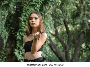 A smug young woman arrogantly points with her finger. Demanding money, gifts etc. A superficial relationship. Outdoor scene.