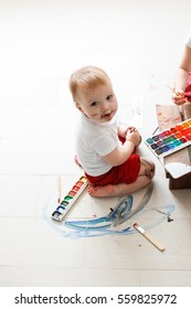 smutty kid Toddler with watercolor paints in red trousers on a light background,