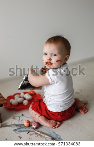 Smutty Kid Toddler With Watercolor Paints In Red Trousers On A Light Background