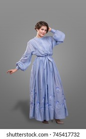 Smyling femail model wear long blue dress isolated over gray background.